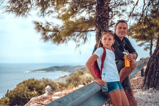 海の海岸線に沿ってハイキングした後休んでいる父と娘