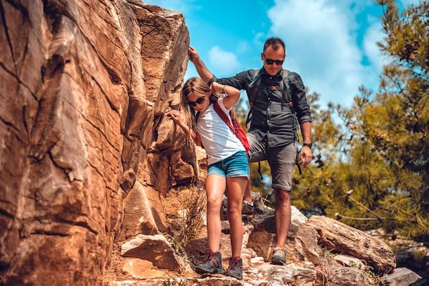 崖から降りる父と娘