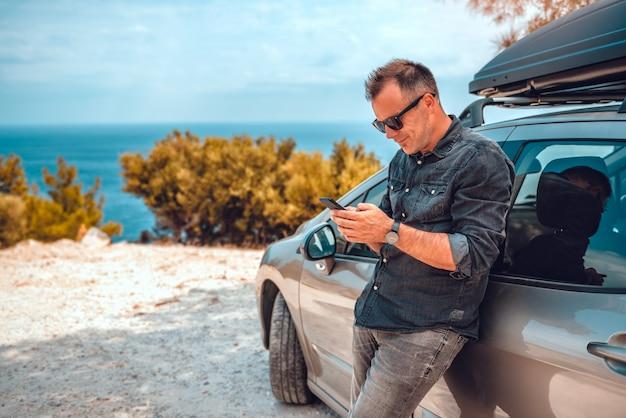スマートフォンを使用して車にもたれる男