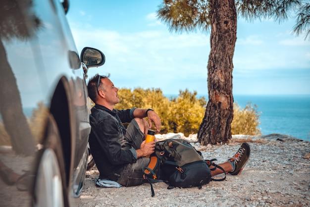 車でハイキングした後休んでいる男