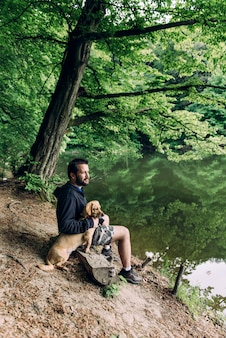 湖のほとりに犬と一緒にベンチに座っている男
