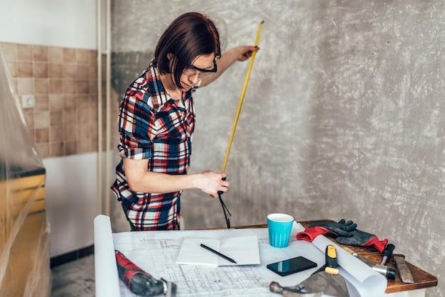 Женщина измеряет стену на кухне