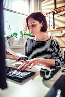 Деловая женщина читает письмо и использует компьютер в офисе