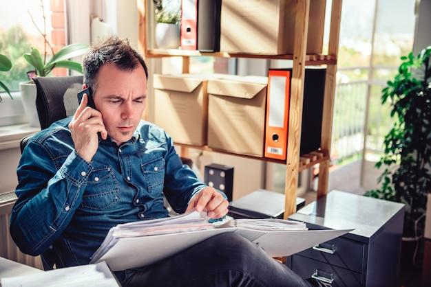 Бизнесмен разговаривает по телефону и ищет папку документов