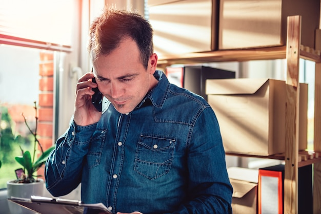 Человек разговаривает по телефону и держит клипборд