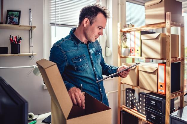 配達のためのパッケージをチェックする男