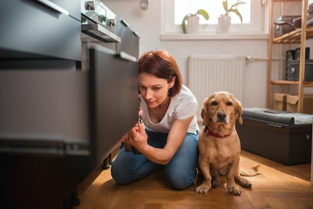 Женщина с собакой строит кухню и использует дрель
