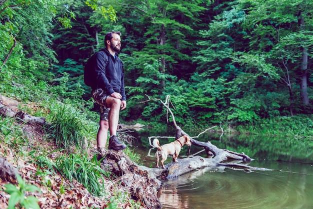 男と彼の犬は湖の岸で休む