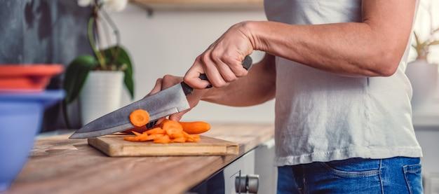 Женщина режет морковь