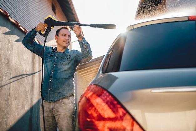 高圧洗浄機で彼の車を洗う人