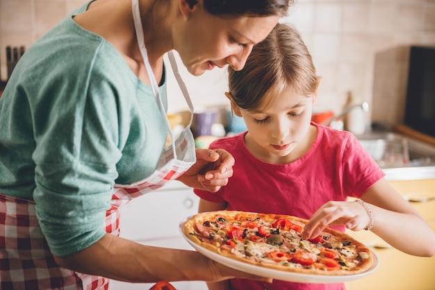 母と娘の新鮮なピザの試飲
