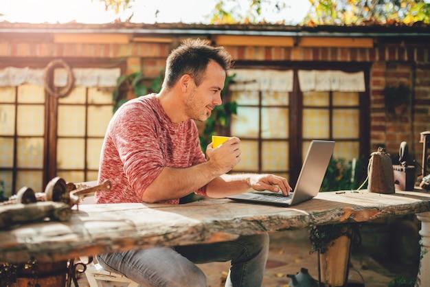 コーヒーを飲みながら、裏庭のパティオでラップトップを使用している男性