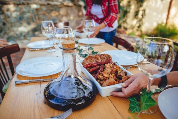 Женщина, подающая мясо барбекю на обеденном столе