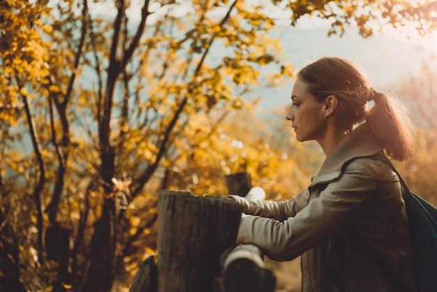 フェンスのそばに立って、景色を楽しみながら山の女性