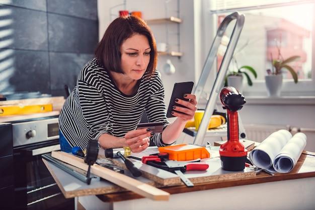 キッチンの改装中にオンラインショッピングをする女性