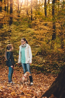 森でのハイキングの犬と母と娘
