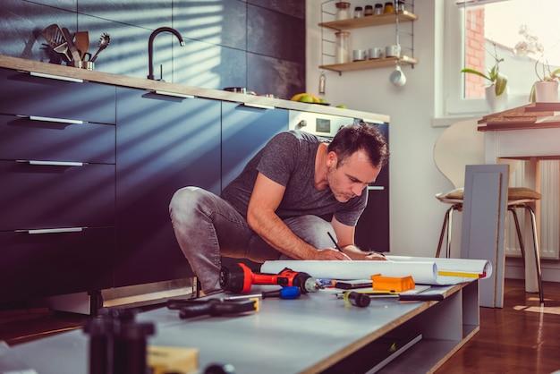 キッチンキャビネットを構築しながら青写真をチェックする男