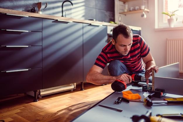 女性のキッチンを構築し、コードレスドリルを使用して