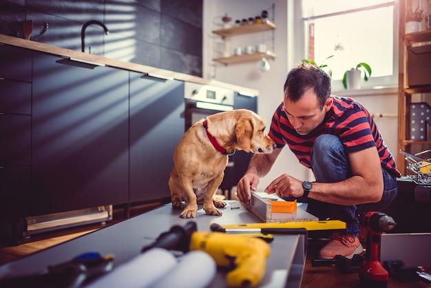 犬のビルのキッチンキャビネットを持つ男