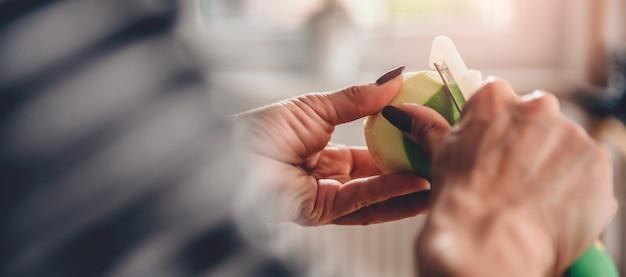 Женщина пилинг яблоки