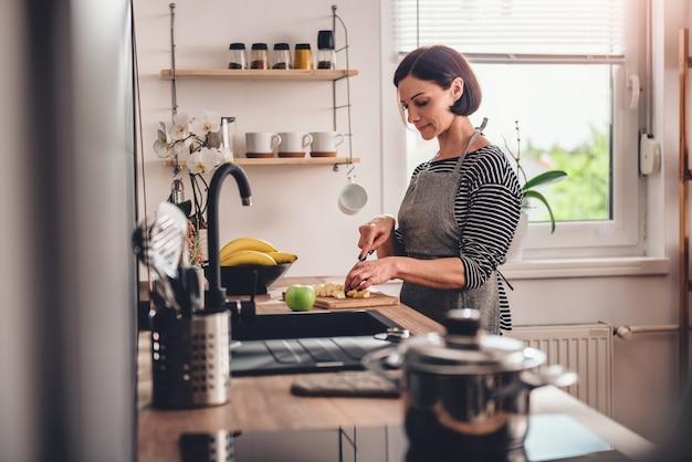 台所で女性切削りんご