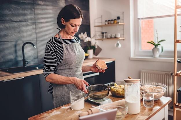 キッチンスケールで女性測定小麦粉