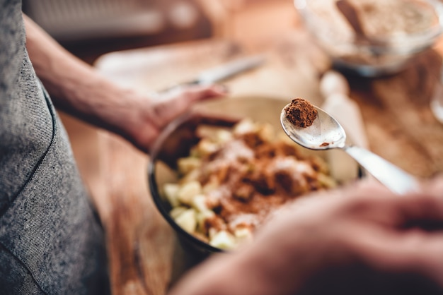 Женщина делает яблочный пирог и добавляя специи