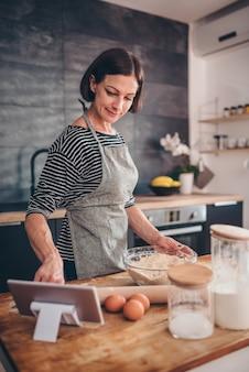 タブレットでアップルパイレシピを検索する女性