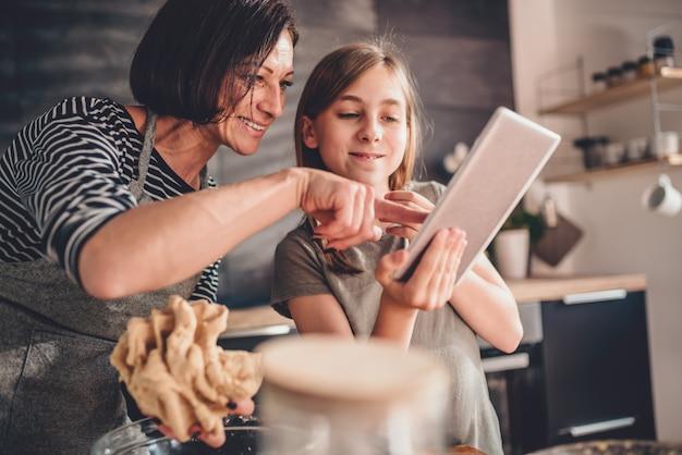 母と娘のタブレットでアップルパイレシピを検索