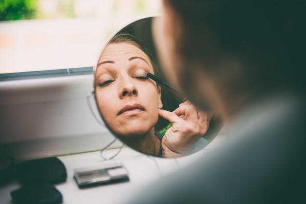 ウィンドウで化粧をしている女性