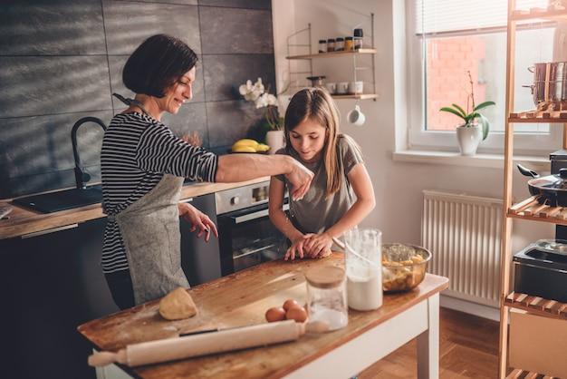 母と娘が木製のテーブルに生地を混練