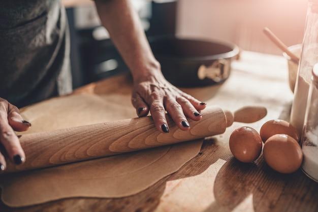 木製のテーブルに生地を圧延女性