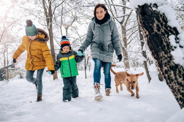 Семья с собакой гуляет по свежему снегу