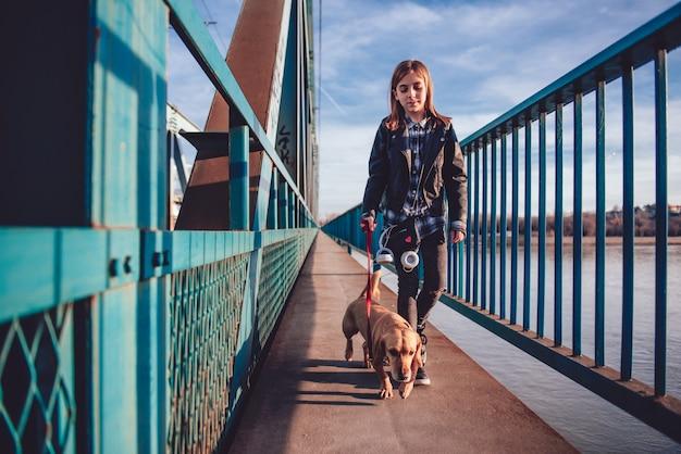 Девушка с собакой гуляет по мосту