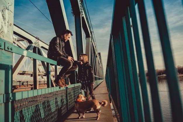 Отец и дочь отдыхают на мосту и разговаривают