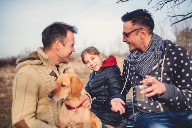 Веселые родители с дочерью и собакой