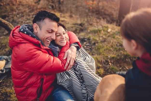 Муж обнимает жену за столом для пикника с дочерью и собакой