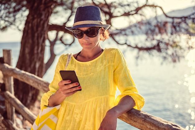 木製のフェンスに立っていると、スマートフォンを使用して女性