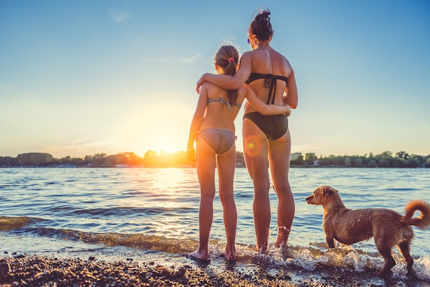 母、娘、ビーチで犬