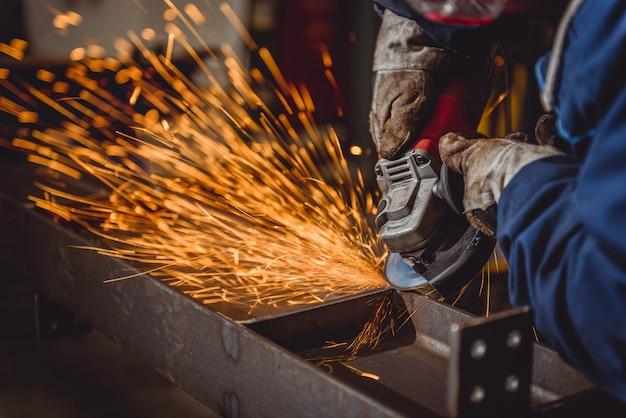 Рабочий, использующий угловую шлифовальную машину