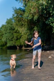 川で彼女の犬と遊ぶ少女