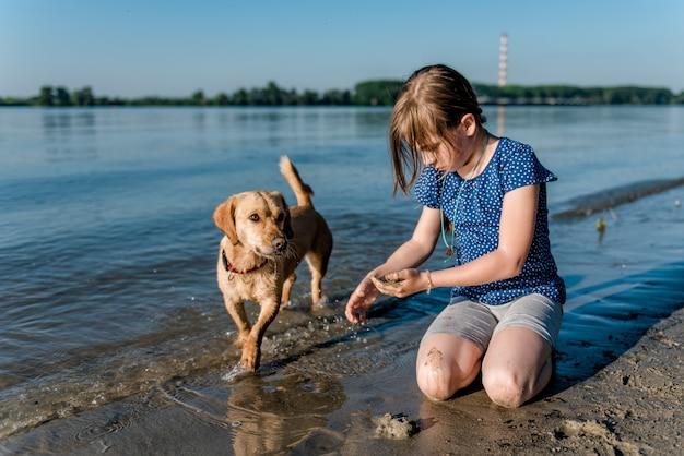 ビーチで遊ぶ犬を持つ少女