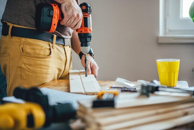 コードレスドリルで木材を掘削男