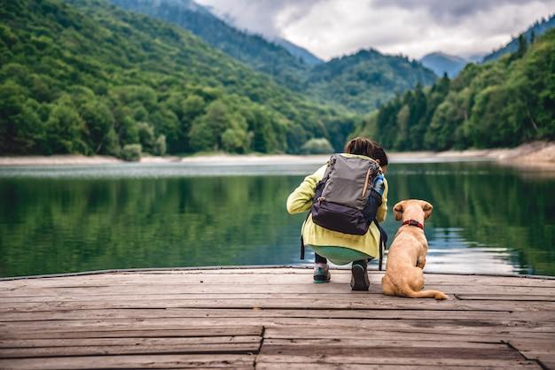 湖の桟橋に立っている犬を持つ女性