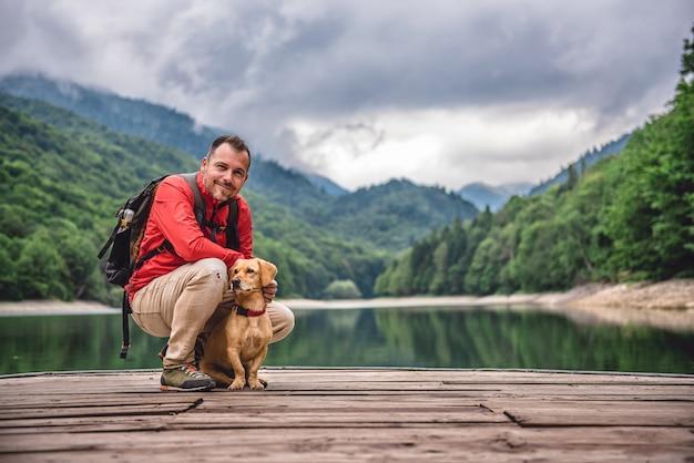 桟橋のポーズで犬とハイカー