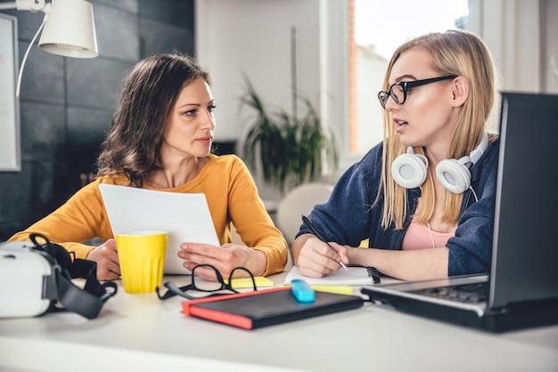 Два деловая женщина с помощью компьютера