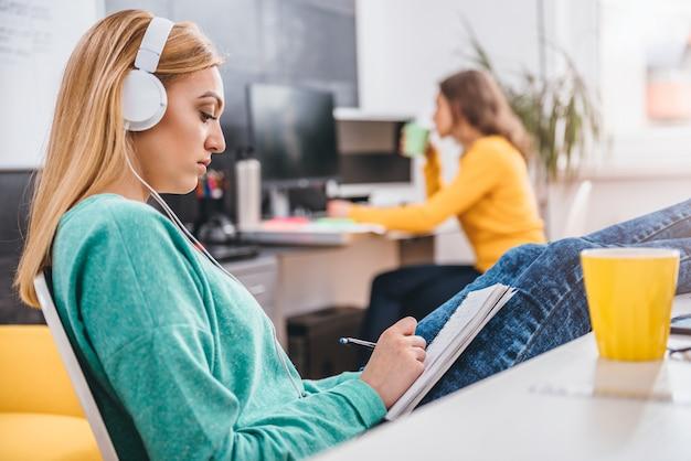 オフィスで音楽を聴く若いビジネス女性