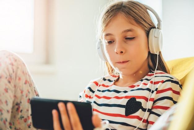 Маленькая девочка сидит на диване и с помощью смартфона