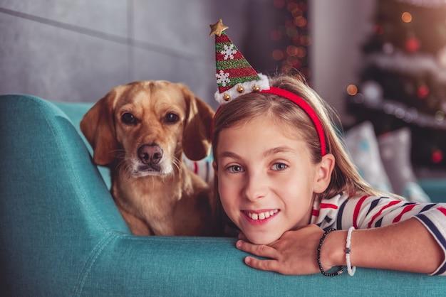 ソファでポーズをとって黄色い犬を持つ少女