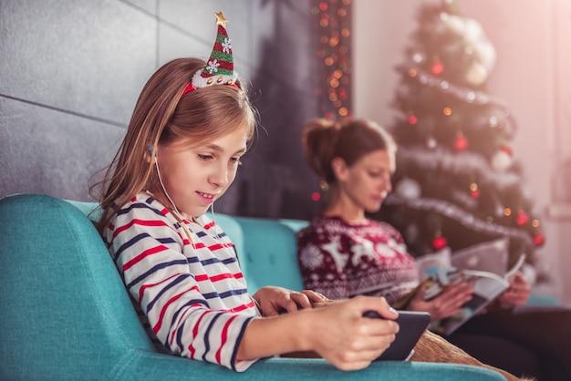 娘と母のクリスマスの間にソファでリラックス